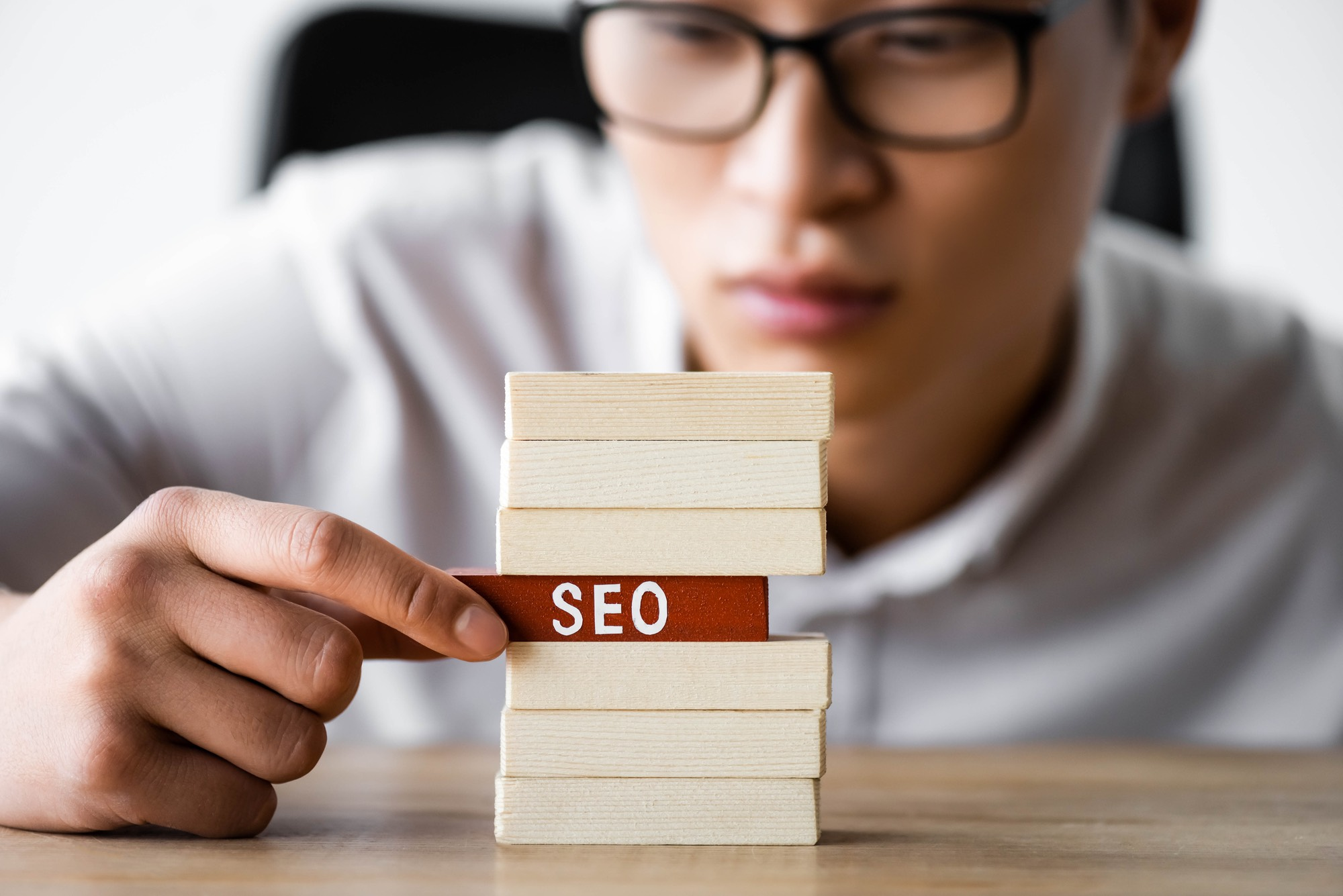 "Man from an SEO content agency pulling out a wooden block labelled ""SEO"" from a stack of blocks"