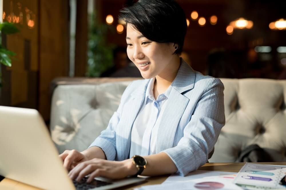A woman smiling and typing on a laptop