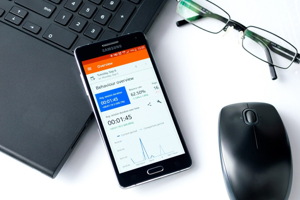 Image of a phone showing Google Analytics and Behaviour overview, which a content marketing agency can analyse and form strategies around.