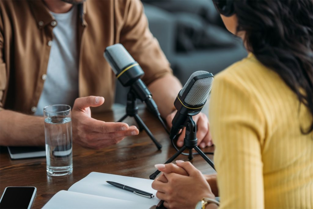 Two people co-hosting a podcast, one of the emerging digital marketing trends.