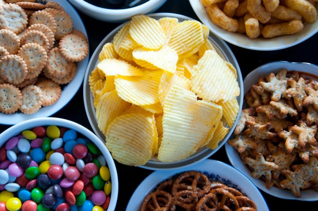 Different sweet and savoury snacks laid out in bowls on a table