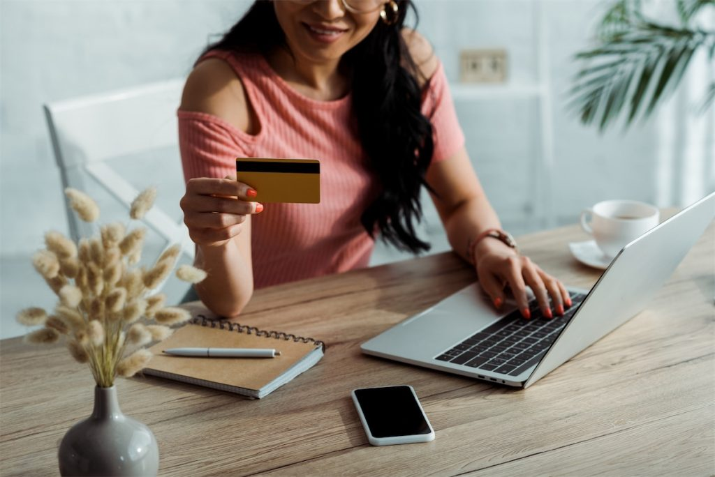 A woman looking at her credit card as she completes her online shopping payment