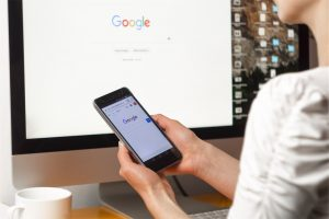 A woman using Google Search on her phone, with Google Search also open on her monitor.