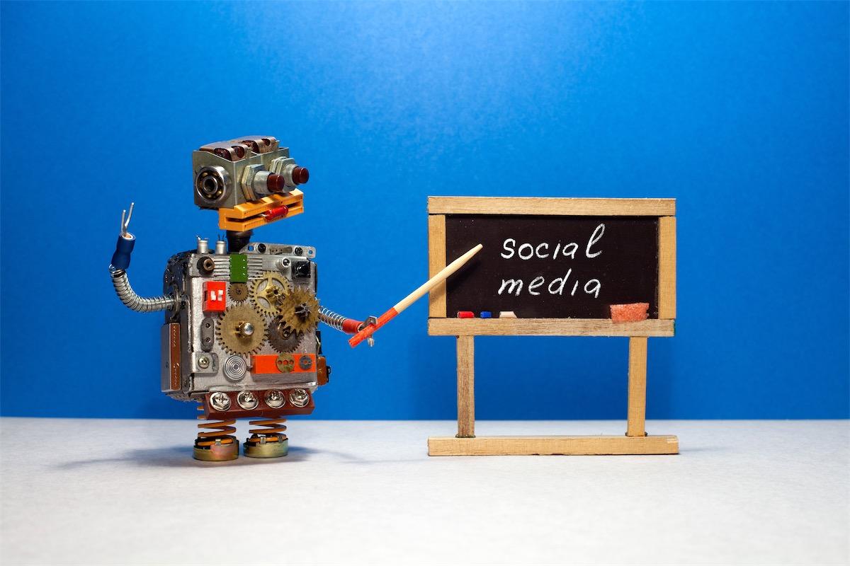 A figurine pointing the words social media, a popular type of digital marketing, written on a blackboard
