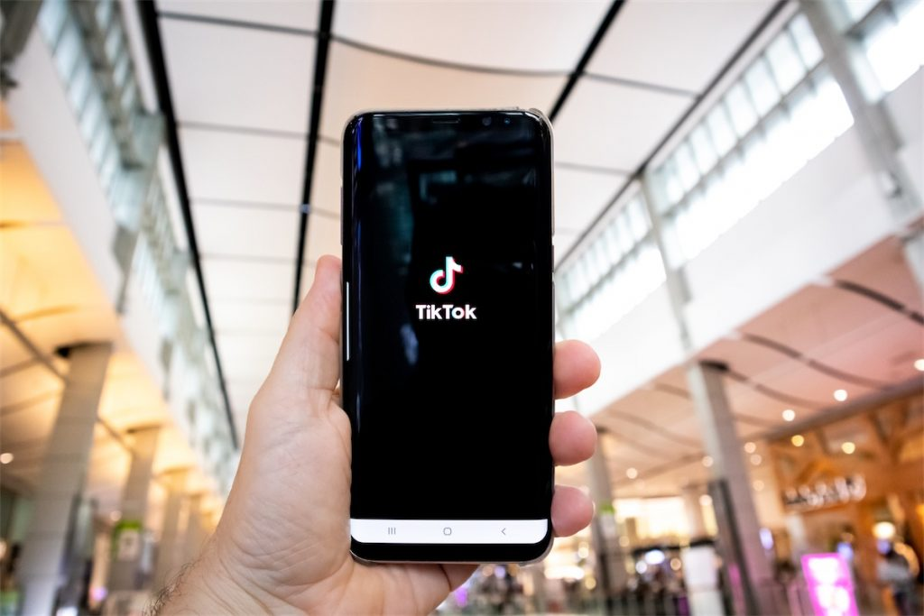A hand holding a smartphone displaying the TikTok app, which Singapore social media statistics indicate to have had over 1 million downloads between January and July 2020