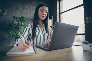 Content marketer tracking SEO content KPIs on her laptop