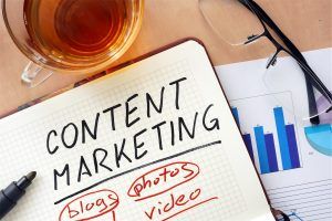 "A notebook with the words ""content marketing"", ""blogs"", ""photos"", and ""video"" written on it"